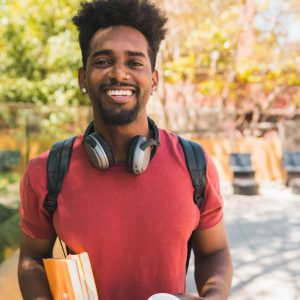 Afro university student holding his books.